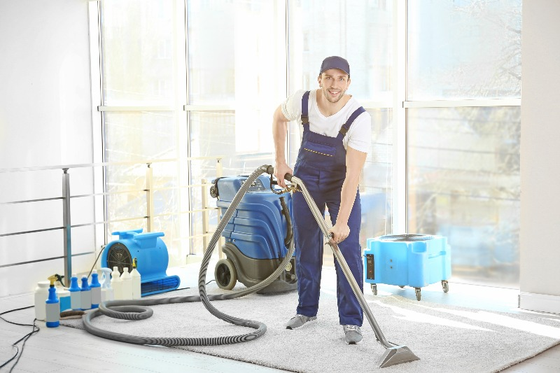 worker with carpet cleaning equipment